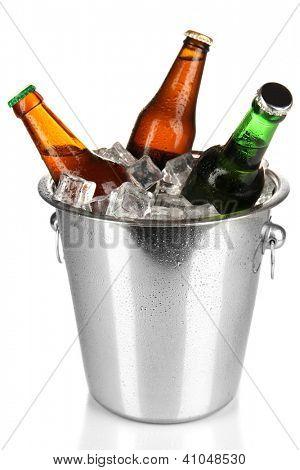 Botellas de cerveza en el cubo de hielo aislado en blanco