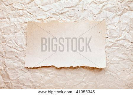 Ripped Piece Of Paper On Old Crushed Paper Background. Vintage Retro Card