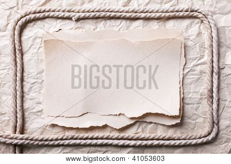Ripped Piece Of Paper And Rope On Old Crushed Paper Background. Vintage Retro Card