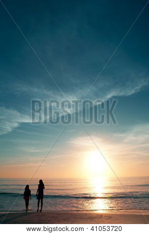 Two little girls on beautiful beach during sunset.