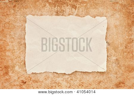 Ripped Piece Of Old Paper On Grunge Paper Background. Vintage Retro Card