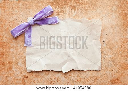 Ripped Piece Of Paper With Purple Bow On Grunge Paper Background. Vintage Retro Card