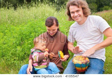 Eltern und Baby auf Natur mit Musikinstrumenten