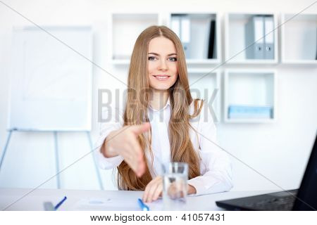 Portrait Of Beautiful Young Smiling Business Woman Sitting At Desk Offering A Handshake In Bright Of