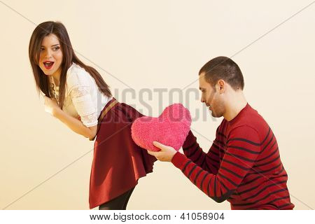 Couple in love fooling around while girl is surprised