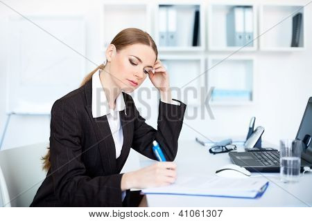 Portrait Of A Beautiful Young Business Woman In The Office Doing Some Paperwork