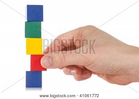 Hand Establishes A Wooden Cube