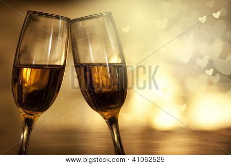 Two champagne glasses on golden background with heart shaped bokeh