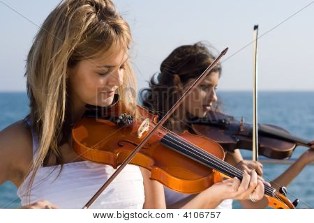 Two Violinists Play Violins On The Beach