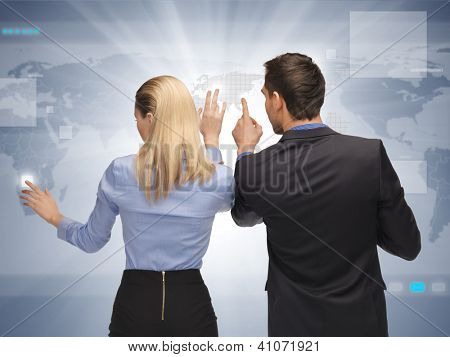 picture of man and woman working with virtual touch screens.