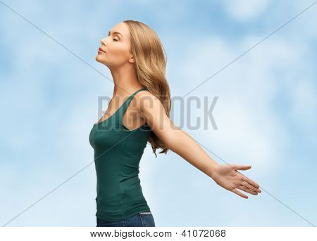 picture of happy woman spreading hands over blue sky.
