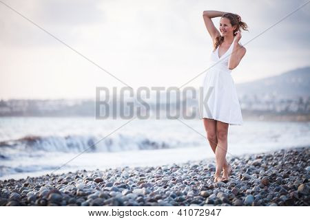 Young woman on the beach enjoying a warm summer evening