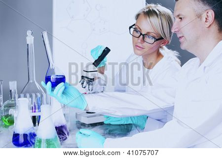 two scientist in chemical lab conducting experiments