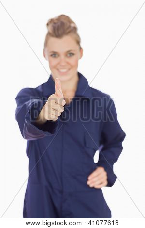 Portrait of young female technician gesturing thumbs up over white background