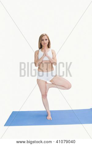 Portrait of young woman standing in praying position over white background