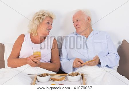 Happy aged couple eating breakfast lying on the bed