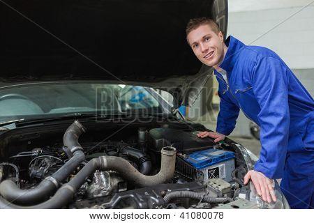 Portrait of male mechanic working under car bonnet
