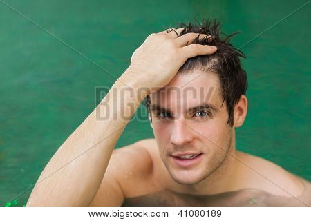 Happy man touching his hair in the swimming pool