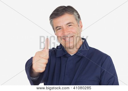 Portrait of happy mature mechanic showing thumbs up sign over white background