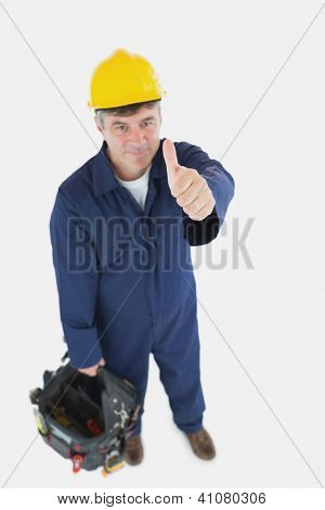 High angle view of mature man with tool bag showing thumbs up sign over white background