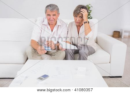 Old stressed couple calculating bills in sitting room