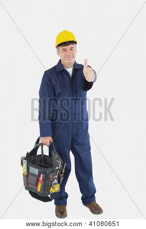 Full length portrait of mature mechanic with tool bag showing thumbs up sign over white background