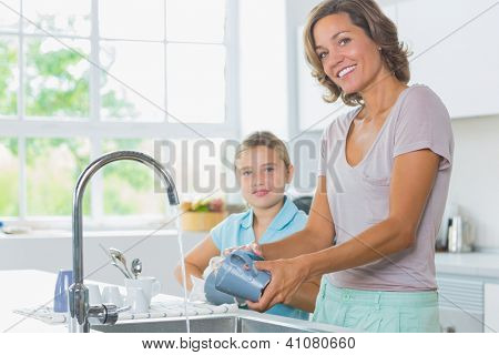 Happy mother and daughter doing the washing up together in kitchen
