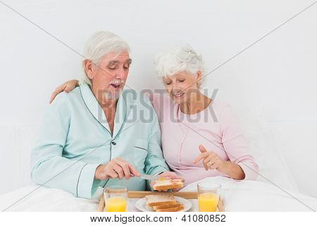 Happy old couple having breakfast in bed