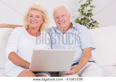Old couple using a laptop together sitting on the sofa