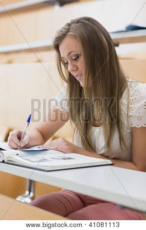 Focused student sitting at the lecture hall writing notes