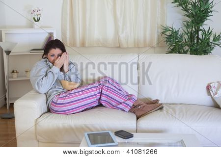 Scared young woman covering face while watching a horror film at home