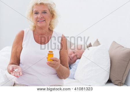 Old woman with the opened pill bottle with a man sleeping on the bed