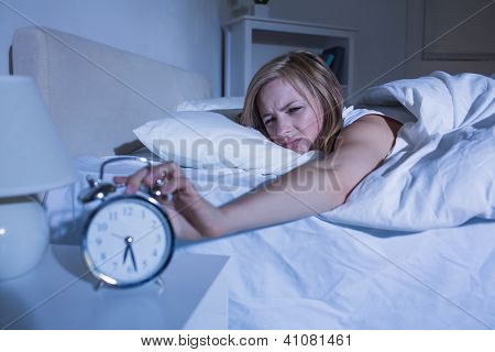 Displeased young woman in bed extending hand to alarm clock at home