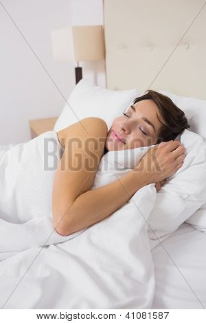 Smiling woman sleeping comfortably in bed in hotel room