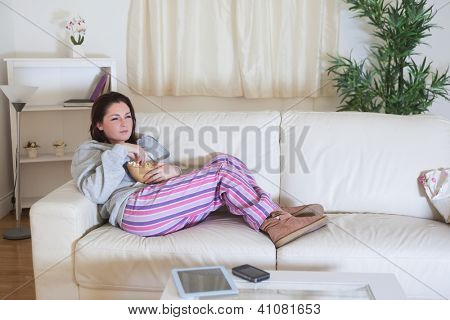 Relaxed young woman with bowl of popcorn watching tv at home