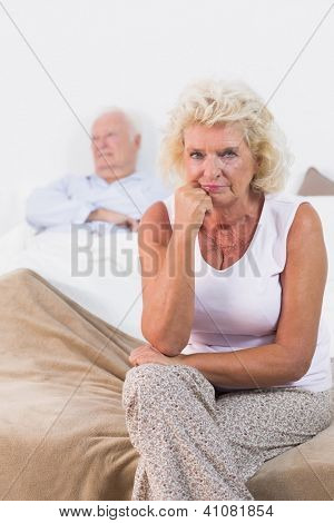 Disappointed old woman sitting on the bed
