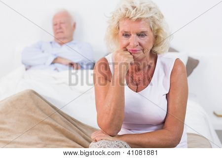 Discouraged old woman sitting on the bed with old man sleeping