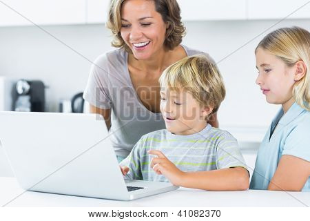 Mother using laptop with her children in the kitchen
