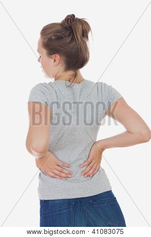 Rear view of young woman suffering from back pain against white background