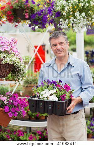 Smiling customer taking flower boxes outside in garden center
