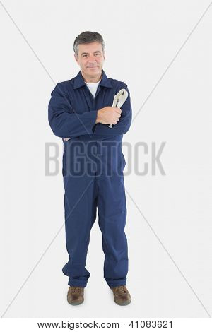 Portrait of mature technician holding locking pliers over white background