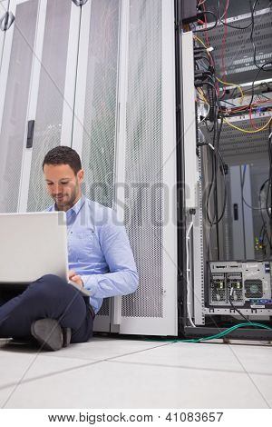 Man working with his laptop on the floor beside servers in data center