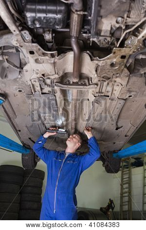 Male auto mechanic examining car using flashlight