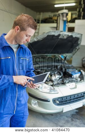 Male mechanic using digital tablet with car in background