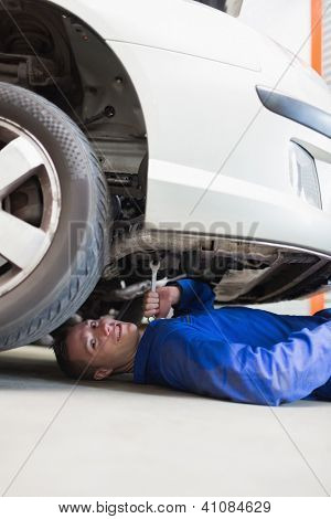 Portrait of male auto mechanic working under car