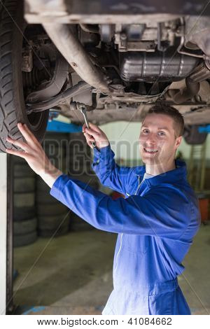 Portrait of male mechanic in coveralls working under car