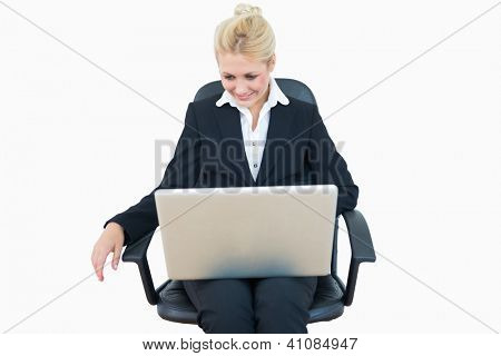 Happy young business woman using laptop on chair over white background