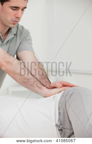 Serious chiropractor pressing the hip of his patient in a room