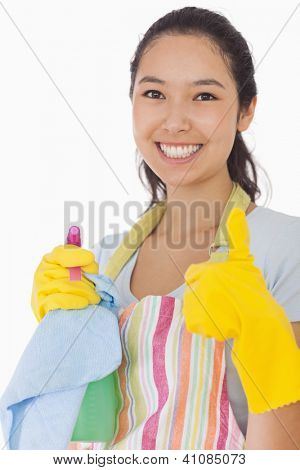 Smiling woman with cleaning products giving thumbs up in rubber gloves