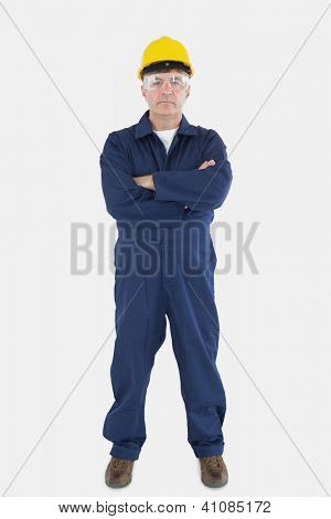 Full length of confident technician wearing hardhat and eyewear standing against white background